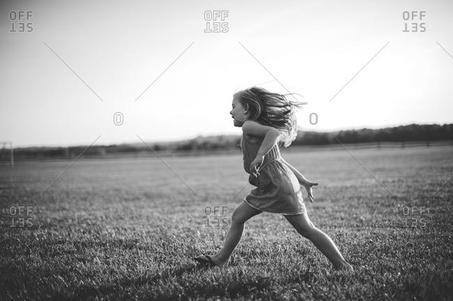 A little girl runs across a grassy field