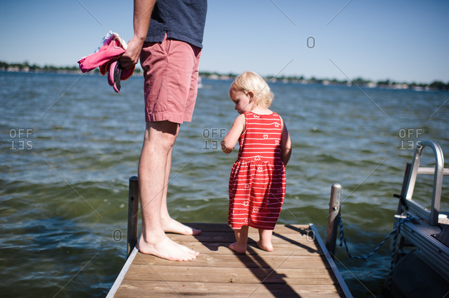 A father and toddler stand on a dock