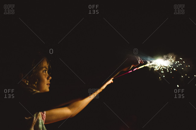 A girl plays with sparklers
