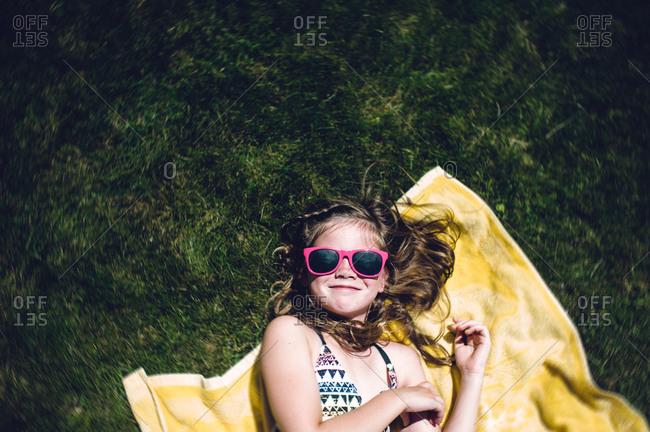 A girl sunbathes on grass