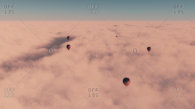 Four hot air balloons floating above dense cloud