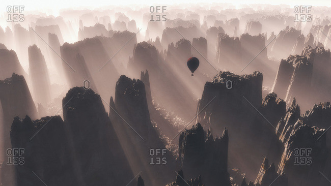 Hot air balloon flying over rough mountain range at sunrise