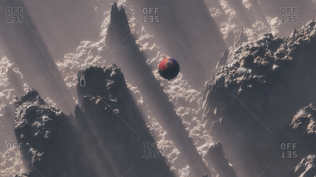 Hot air balloon flying between peaks in mountain range