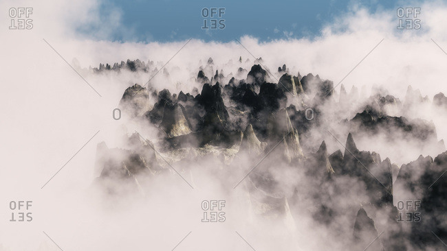Aerial view of rough rock formation peeking through cloud layer