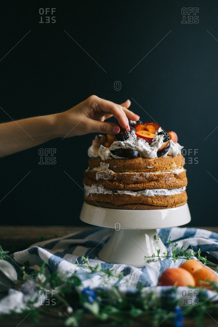 A woman adds fruit to a layer cake