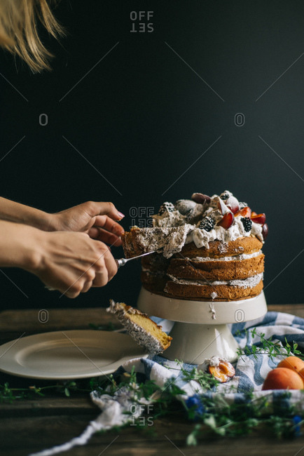 A woman serves slices of layer cake
