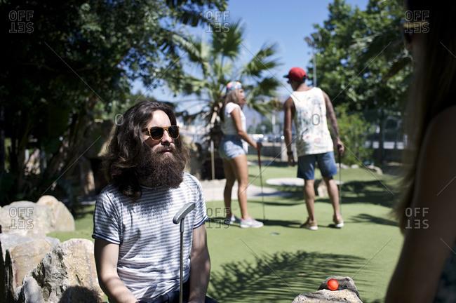 Man sitting near friends during mini golf game