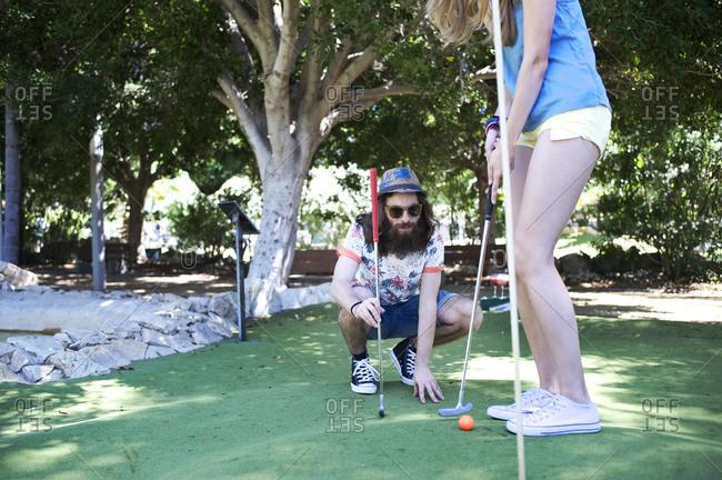 Man watching woman take shot during mini golf