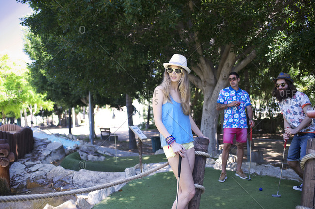 Three friends staring at shot during mini golf game