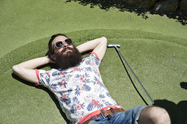 Man lying on green in mini golf course