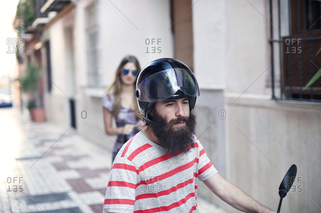 Man sitting on a scooter with woman behind him