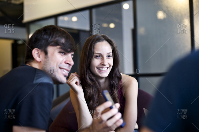 Coworkers smiling with cell phone