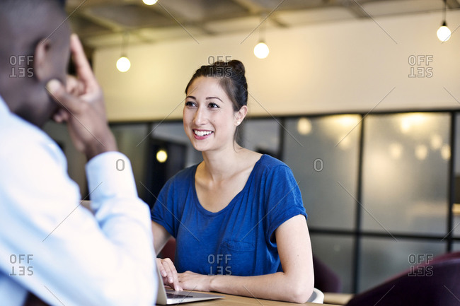 Multi ethnic coworkers smiling at table with laptop