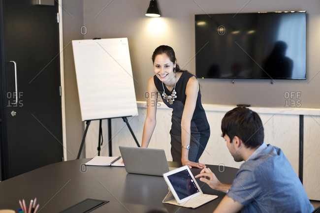 Man and woman using technology during office meeting