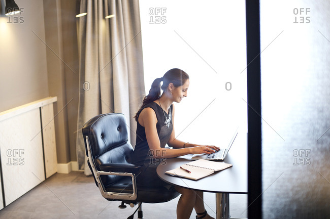 Woman sitting at table with her laptop in an office