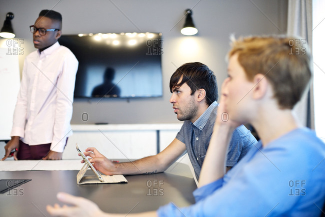 Three coworkers listening during office meeting