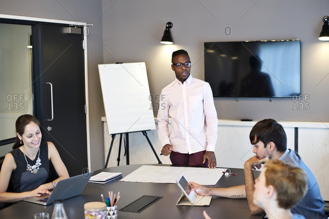 Man leading meeting while coworkers use technology