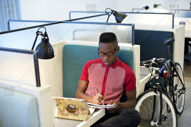 Man writing notes at his cubicle space