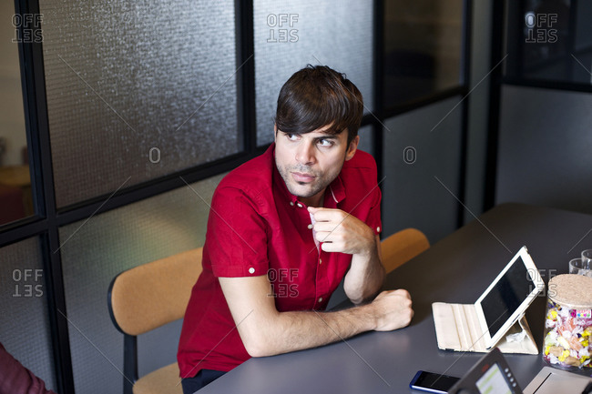 Man with tablet listening during office meeting