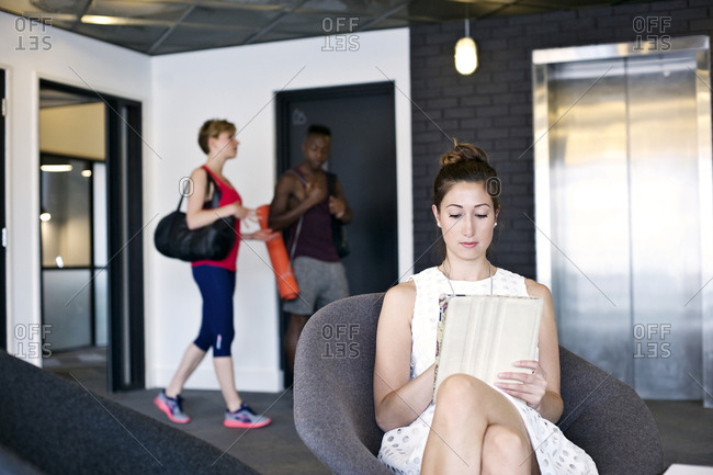 Employees in exercise gear by colleague using tablet