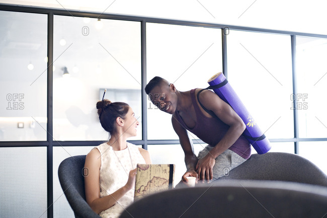Man with yoga mat talking to female coworker