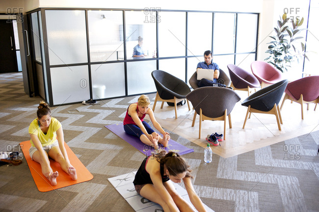 Office workers stretching on yoga mats