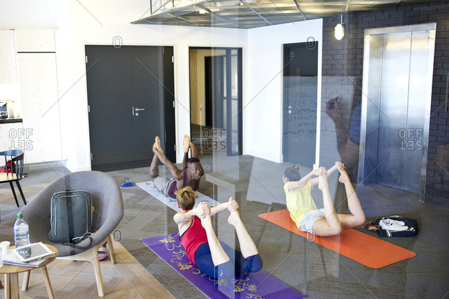 Office employees stretching on yoga mats