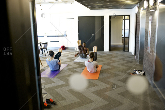 Employees doing yoga in office
