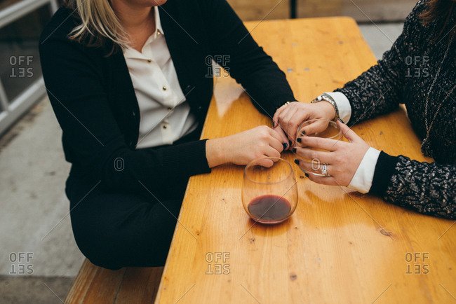 A couple holds hands on an outdoor patio at a wine bar