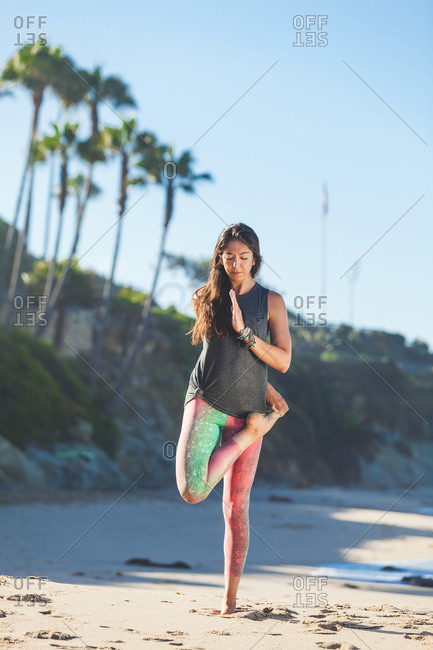 A woman practices yoga on the sand