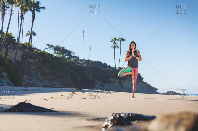 A woman holds a yoga pose on the beach