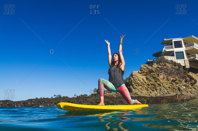 A woman holds a yoga pose on a paddleboard