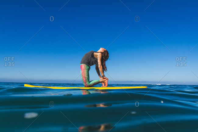 A woman holds a backbend yoga pose on a yellow paddleboard