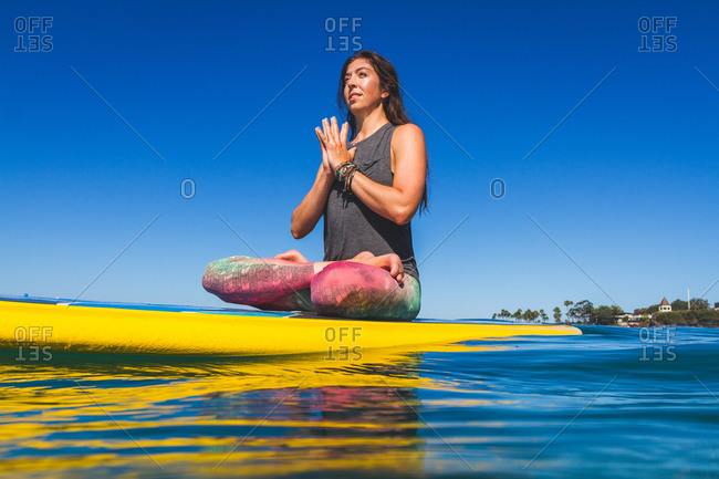A woman sits in a meditative pose on a paddleboard