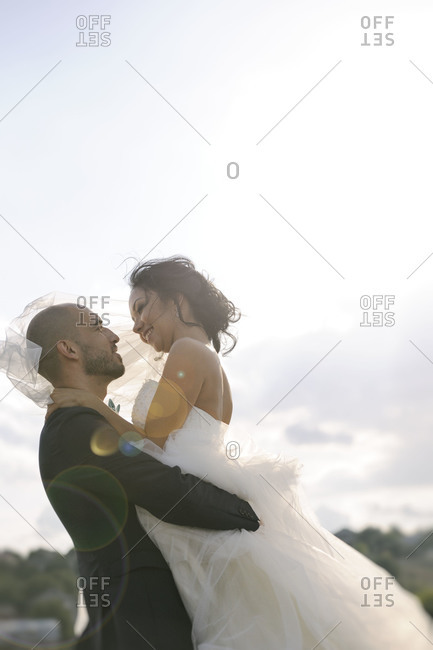 A groom lifts the bride