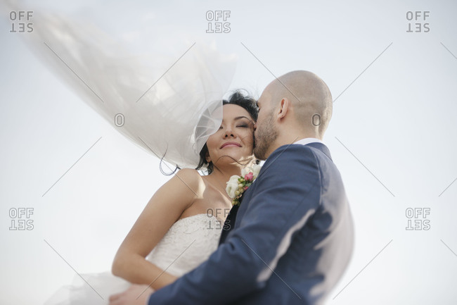 A groom kisses his bride on the cheek