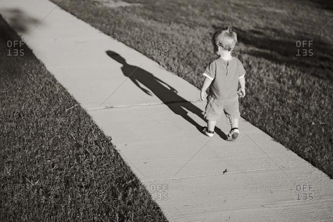 A toddler boy walks on a sidewalk