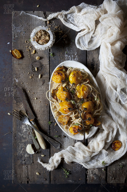 Spaghetti with roasted yellow cherry tomatoes and pine nuts