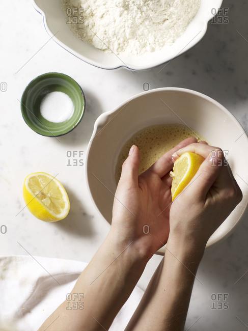 Hands squeezing lemon juice into a bowl