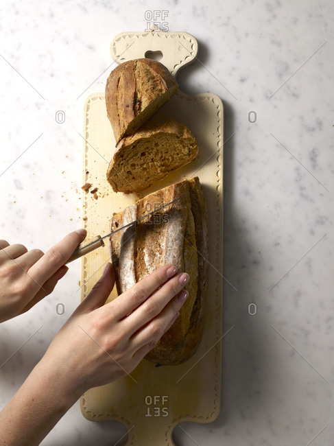 Overhead view of hands slicing a loaf of bread on cutting board