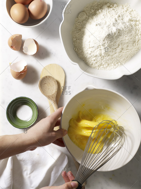 Overhead view of hands beating eggs with a whisk