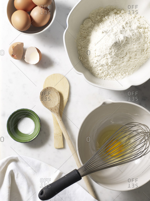 Overhead view of bowl of flour and eggs with whisk and wooden spoon