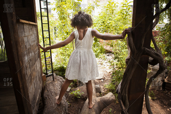 Girl climbing on tree roots