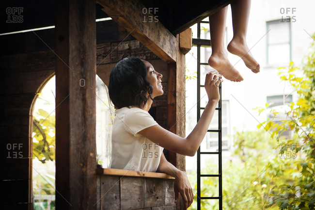 Mother and daughter having fun in a tree house