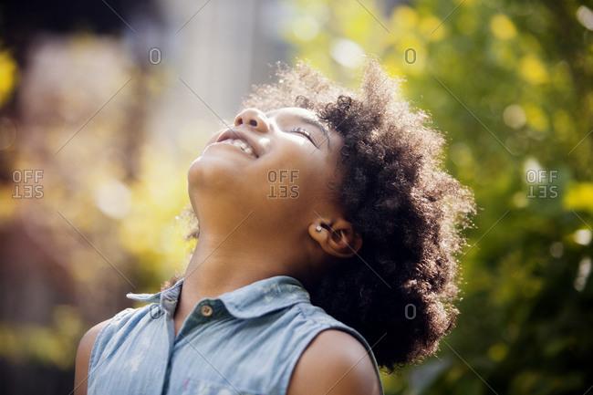 Girl throwing her head back and enjoying the sun