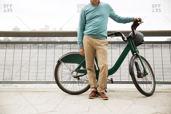 A man stands by a river with a shared bike