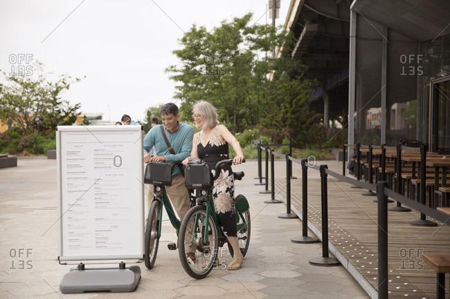 A couple riding shared bikes checks out a restaurant menu