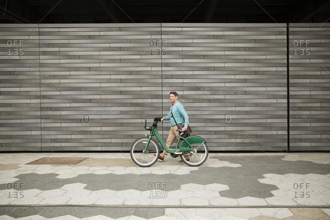 A man walks his shared bike down a sidewalk