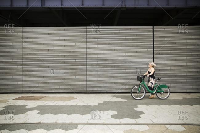 A woman walks her shared bike down a sidewalk