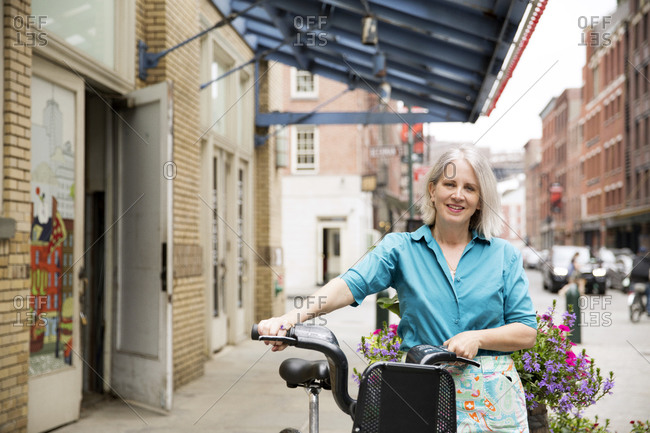 A woman walks her shared bike down a city street
